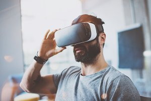 Attractive bearded man wearing virtual reality glasses in modern interior design coworking studio. Smartphone using with VR goggles headset. Horizontal,flares effect, blurred background.