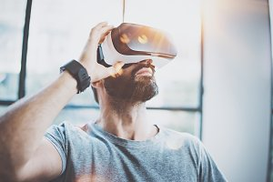 Attractive bearded man enjoyingvirtual reality glasses in modern interior design coworking studio.Home play concept.Smartphone use with VR goggles headset.Flare and sunny effect,blurred background.