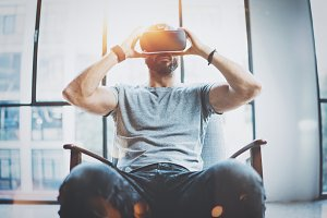 Attractive bearded man enjoyingvirtual reality glasses in modern interior design coworking studio.Home play concept.Smartphone use with VR goggles headset. Front view,flare effect,blurred background.