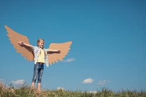 Little girl playing with toy wings