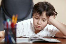 School boy studies hard over his