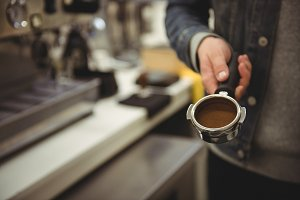 Man holding portafilter with ground coffee