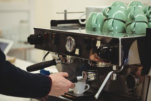 Hand of man holding portafilter under coffee machine