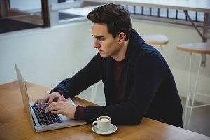 Man using laptop while having coffee