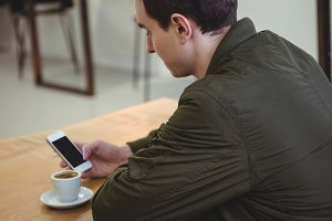 Man using phone while sitting in coffee shop
