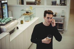 Man talking on his mobile phone while holding a coffee cup