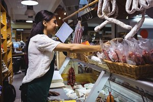 Female staff working at meat counter