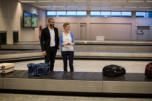 Couple waiting for luggage in baggage claim area