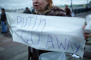 Woman holds a placard Putin Go Away.