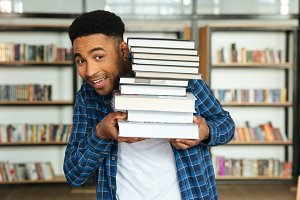 Young afro american male student holding stack of books
