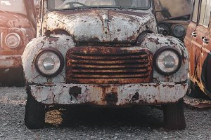 Detail of the front headlight of an rusty car