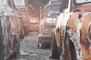 rows of cars in a salvage yard facing each other