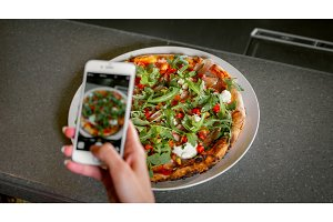 woman photographs pizza at the phone