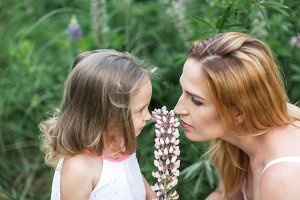 Mom and daughter sniffing flowers