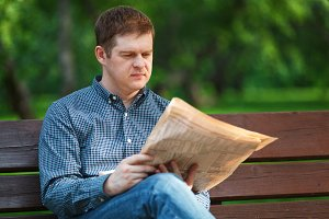 Man reads newspaper on bench park