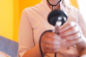Nurse with stethoscope looks patient