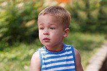 Cute boy sitting on the curb