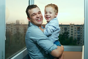 Young father and son smiling balcony