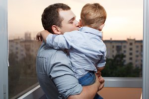 Father kisses his son on the balcony