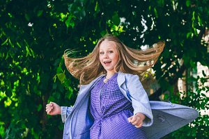 Laughter and joy in the child. Long hair on the move of a little girl