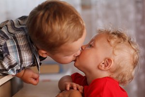 Two little brothers are kissing.
