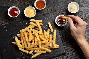 Hand dipping fries in the sauce