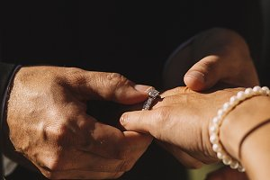 Groom puts a ring on bride's hand