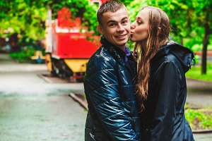 The guy looks in surprise. The girl reaches out to kiss the guy. walk in the park