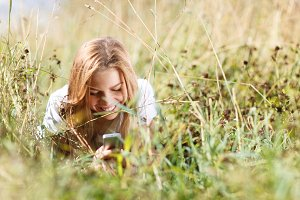 Girl writing sms phone lying grass