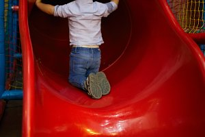 Boy is sitting at slide hole