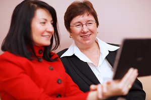 Two women sharing a tablet computer