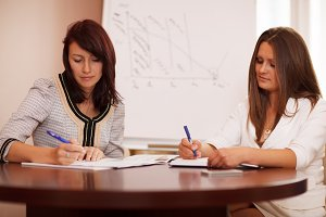 Two women taking notes business