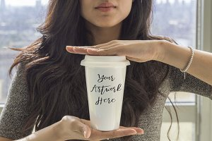 Woman holding blank ceramic mug