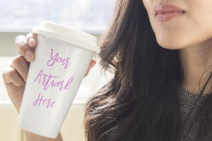 Woman holding blank travel mug