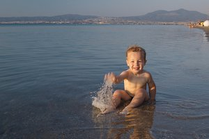 Cute little boy splashing sea