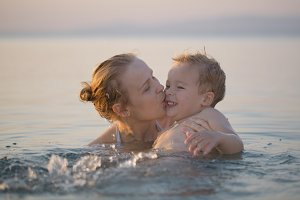 Mother playing sea with little son