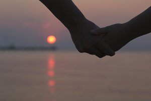 Couple holding hands sunset
