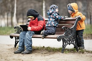 Three young boys playing park bench