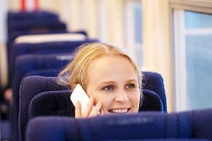Smiling woman talking phone in train