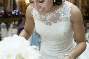 Smiling beautiful bride cutting