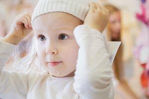 Little girl trying on white caps