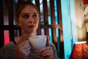 Thoughtful woman holding coffee cup