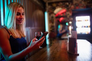 Beautiful woman using mobile phone while having red wine at counter