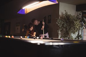 Young happy couple playing pool