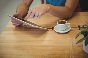 Man using digital tablet with coffee cup on table