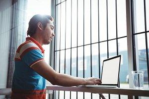 Man using laptop near window