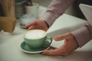 Hands picking cup of coffee