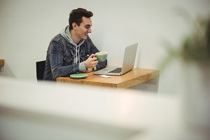 Man looking at laptop while holding coffee