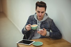 Man using mobile phone while holding coffee cup