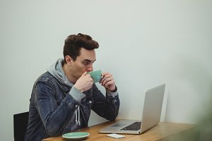 Man drinking coffee while looking at laptop